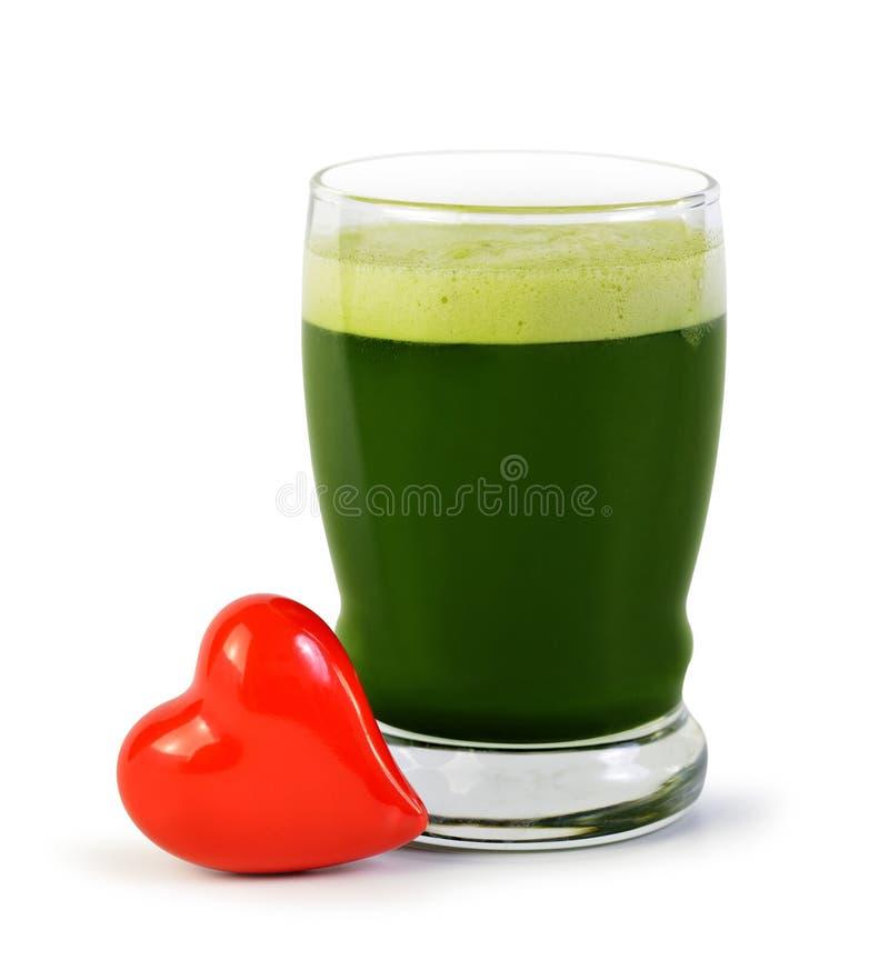 Πράσινο ποτό χυμού κριθαριού στο γυαλί και την κόκκινη καρδιά που απομονώνονται στο άσπρο υπόβαθρο στοκ εικόνες