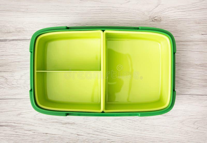 Πράσινο πλαστικό κιβώτιο τροφίμων στο ξύλινο υπόβαθρο στοκ εικόνες