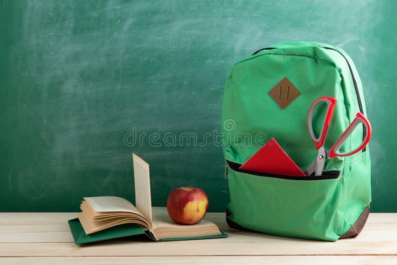 πράσινο σακίδιο πλάτης, ανοικτή βίβλος, κόκκινα σχολικές προμήθειες και μήλο στο υπόβαθρο του πίνακα στοκ φωτογραφίες