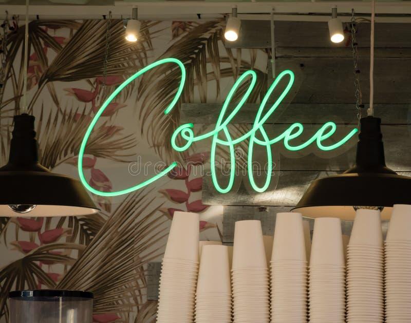 Πράσινο σημάδι νέου με τον καφέ κειμένων στην ταπετσαρία και πίνακες πίσω από τα συσσωρευμένα φλυτζάνια εγγράφου στοκ φωτογραφία με δικαίωμα ελεύθερης χρήσης