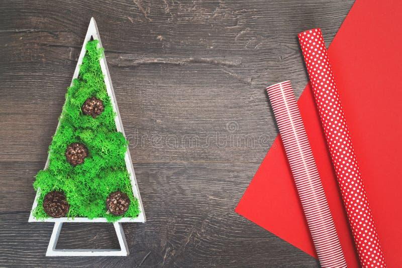 Πράσινο σταθεροποιημένο χριστουγεννιάτικο δέντρο και κόκκινο τυλίγοντας έγγραφο δώρων στοκ φωτογραφία