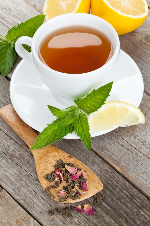 Πράσινο τσάι με το λεμόνι και μέντα στον ξύλινο πίνακα στοκ εικόνες