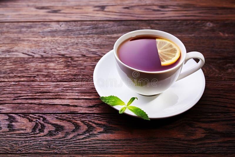 Πράσινο τσάι με το λεμόνι και μέντα στο ξύλινο επιτραπέζιο υπόβαθρο στοκ εικόνες