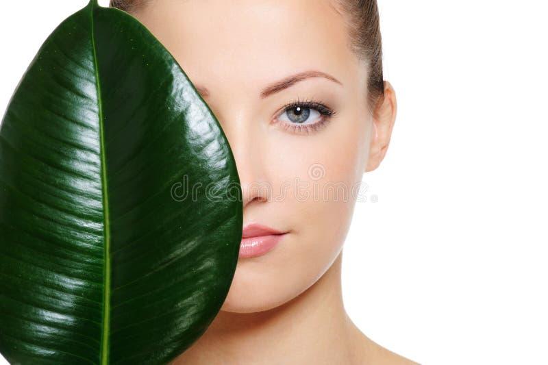 Πράσινο φύλλο που σκιάζει ένα δεύτερο του όμορφου προσώπου γυναικών στοκ φωτογραφία με δικαίωμα ελεύθερης χρήσης