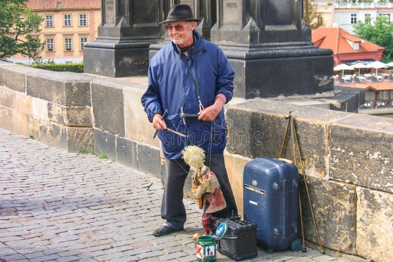 ΠΡΑΓΑ, ΤΣΕΧΙΚΑ - 30 Ιουλίου 2007 - ένας παλαιός κύριος μαριονετών με μια μαριονέτα που αποδίδει στη γέφυρα του Charles πέρα από V στοκ φωτογραφία με δικαίωμα ελεύθερης χρήσης