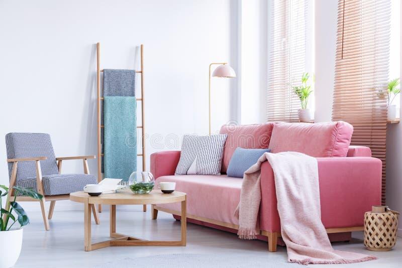 Πραγματική φωτογραφία ένας ρόδινος καναπές με τα μαξιλάρια και κάλυμμα που στέκεται στο α στοκ εικόνα
