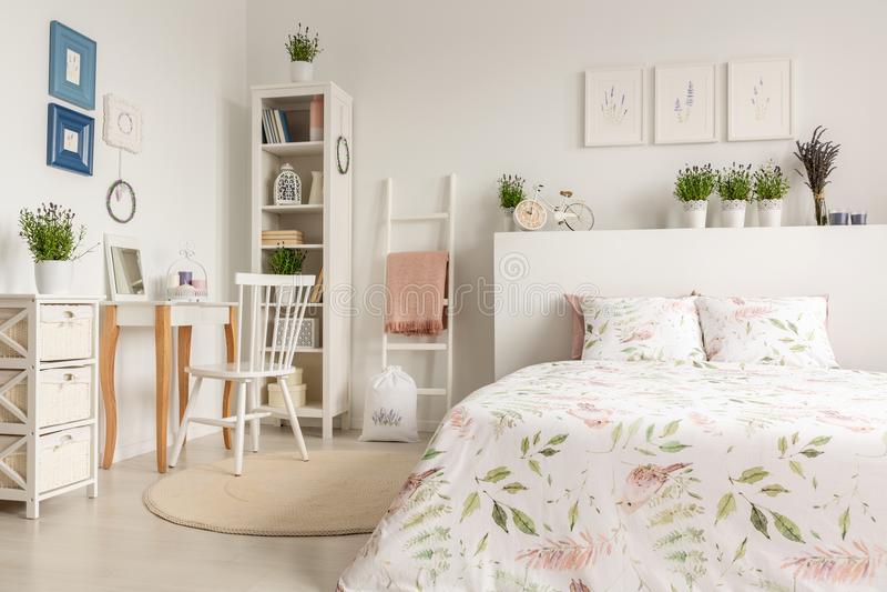 Πραγματική φωτογραφία ενός εσωτερικού κρεβατοκάμαρων κρητιδογραφιών με ένα διπλό κρεβάτι, χλωρίδα στοκ φωτογραφία
