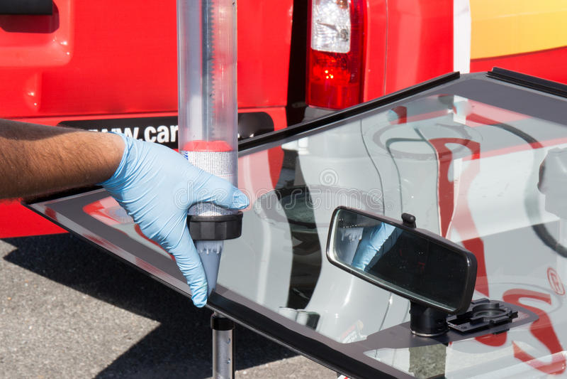 Πραγματικοί μηχανικοί που αλλάζουν το σπασμένο ανεμοφράκτη του αυτοκινήτου στοκ εικόνα