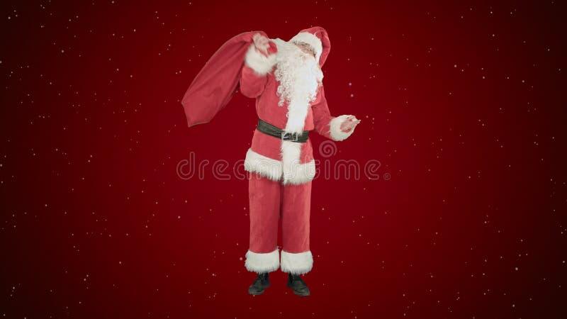 Πραγματικός Άγιος Βασίλης που φέρνει το μεγάλο σύνολο τσαντών των δώρων στο κόκκινο υπόβαθρο με το χιόνι στοκ εικόνα