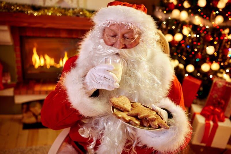 Πραγματικός Άγιος Βασίλης που απολαμβάνει στα εξυπηρετούμενα τρόφιμα στοκ εικόνες