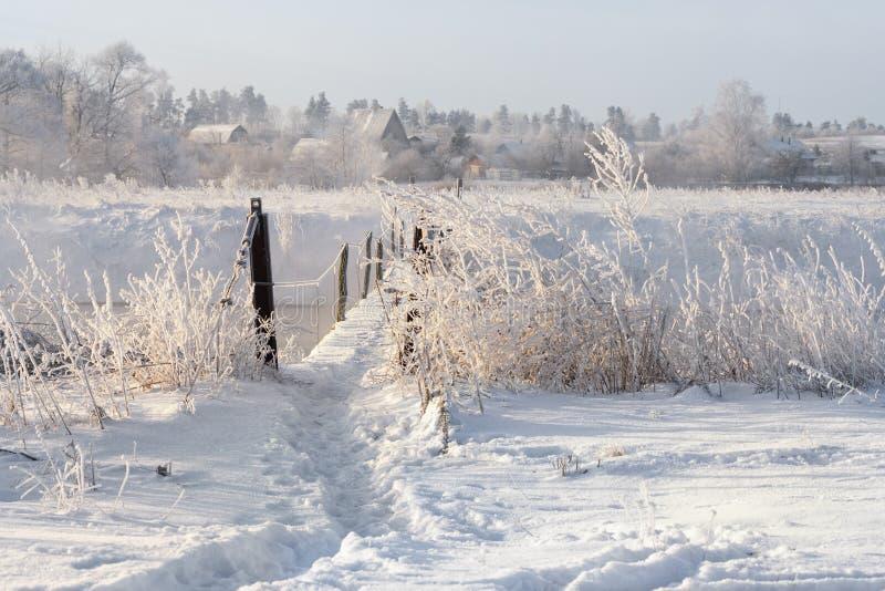 Πραγματικός ρωσικός χειμώνας Χειμερινό τοπίο με το ίχνος πέρα από την επικίνδυνη αγροτική γέφυρα αναστολής πέρα από το χιονώδη ομ στοκ εικόνες με δικαίωμα ελεύθερης χρήσης