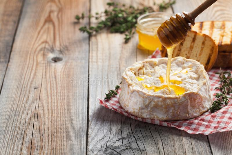 Πραγματικό Camembert από τη Γαλλία με το θυμάρι, το μέλι και το ψημένο ψωμί στον παλαιό ξύλινο αγροτικό πίνακα Μαλακό τυρί WI ενό στοκ εικόνα με δικαίωμα ελεύθερης χρήσης