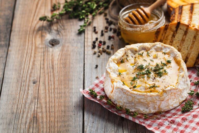 Πραγματικό Camembert από τη Γαλλία με το θυμάρι, το μέλι και το ψημένο ψωμί στον παλαιό ξύλινο αγροτικό πίνακα Μαλακό τυρί WI ενό στοκ φωτογραφίες με δικαίωμα ελεύθερης χρήσης