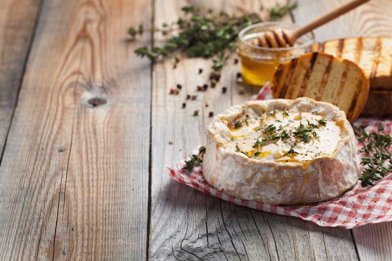 Πραγματικό Camembert από τη Γαλλία με το θυμάρι, το μέλι και το ψημένο ψωμί στον παλαιό ξύλινο αγροτικό πίνακα Μαλακό τυρί WI ενό στοκ φωτογραφίες