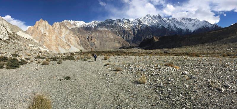 Πραγματοποιώντας οδοιπορικό το ίχνος σε Passu παρουσιάστε landform ξηρασίας, καλυμμένα χιόνι βουνά στη σειρά Karakoram στοκ εικόνες