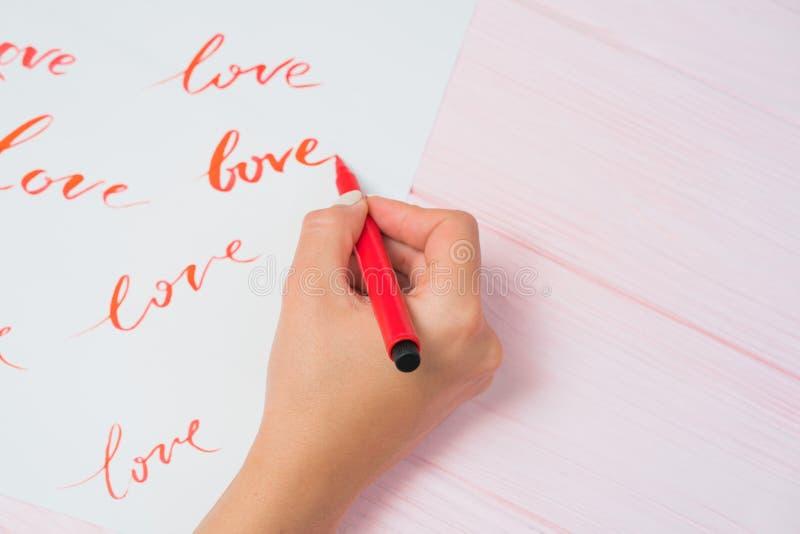 Πρακτικές σπουδαστών καλλιγράφων στο γράψιμο της ΑΓΑΠΗΣ λέξης με τον κόκκινο δείκτη στον καμβά Δημιουργικός καλλιτέχνης freelance στοκ εικόνες