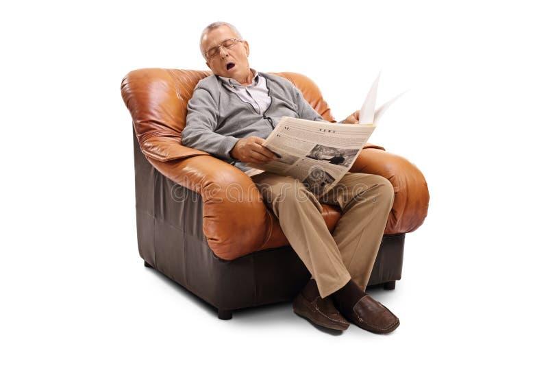 Πρεσβύτερος που κρατά μια εφημερίδα και έναν ύπνο στοκ φωτογραφίες