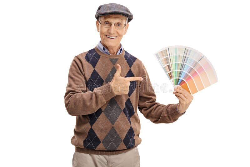 Πρεσβύτερος που κρατά swatch και μια υπόδειξη χρώματος στοκ εικόνες
