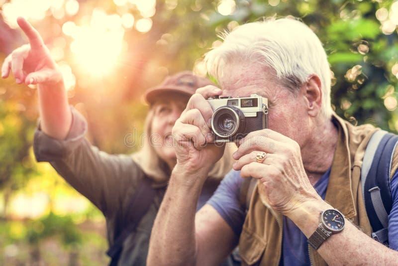 Πρεσβύτερος trekker που παίρνει μια φωτογραφία με μια κάμερα ταινιών στοκ φωτογραφία