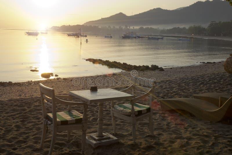 πρεσών Ένας πίνακας και καρέκλες στην παραλία θαλασσίως σε μια βόρεια περιοχή του νησιού στο ηλιοβασίλεμα στοκ φωτογραφία με δικαίωμα ελεύθερης χρήσης