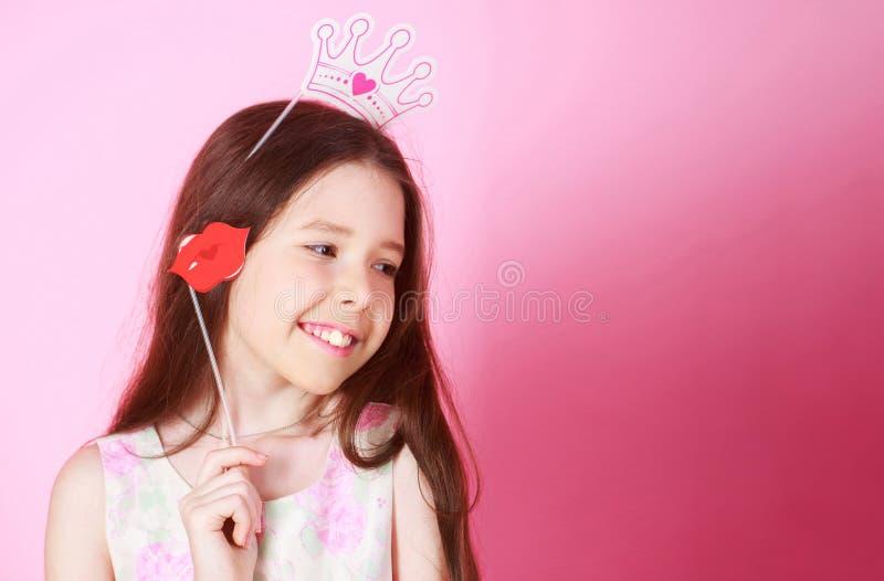 Πριγκήπισσα μικρών κοριτσιών, χείλι, κορώνα, στο ρόδινο υπόβαθρο Εορτασμός καρναβάλι για τα παιδιά, γιορτή γενεθλίων χαριτωμένος στοκ εικόνα με δικαίωμα ελεύθερης χρήσης