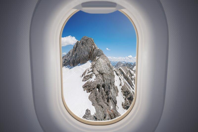 Προβολή από το παράθυρο αεροπλάνου στα βουνά των Άλπεων στοκ εικόνα