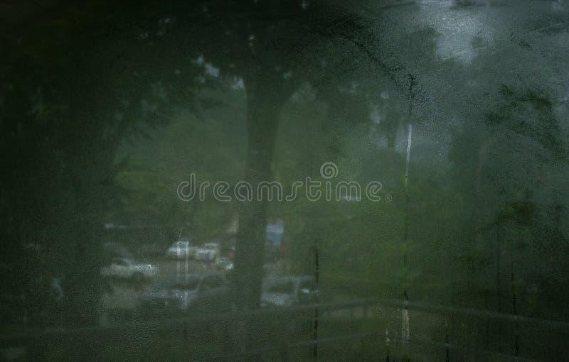 Προβολή σε υγρό γυαλί παραθύρου με σταγόνες βροχής στοκ εικόνες