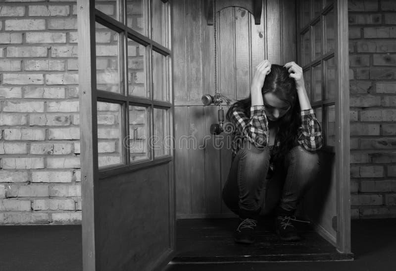 Προβληματική γυναίκα που σκύβει δημόσια τον τηλεφωνικό θάλαμο στοκ φωτογραφία με δικαίωμα ελεύθερης χρήσης