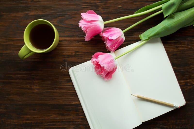 Προγευματίστε φλυτζάνι Α του τσαγιού, λουλούδια, σημειώσεις στοκ εικόνες
