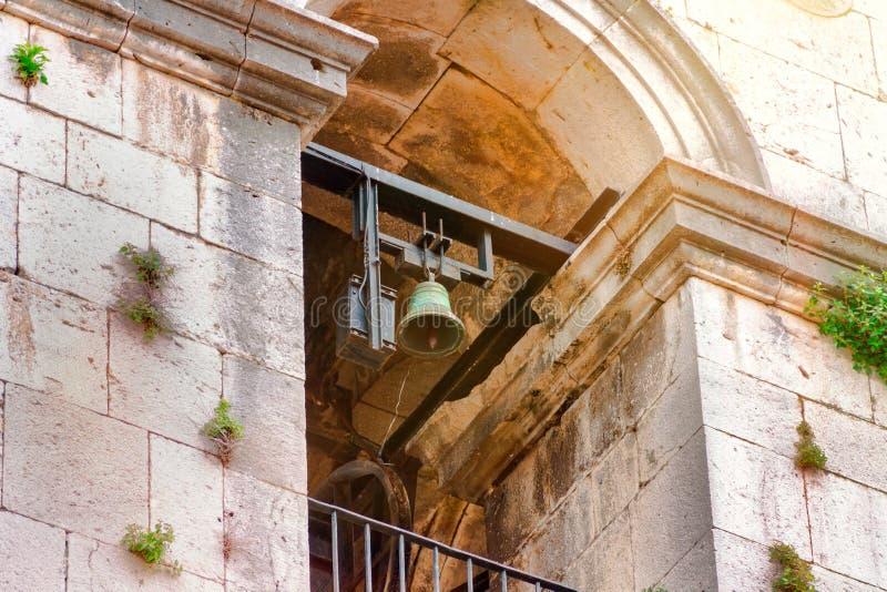 Προγονικός πύργος κουδουνιών και ένα κουδούνι σε μια παλαιά εκκλησία, μια εκκλησία που φωτίζεται από τον ήλιο στοκ φωτογραφία