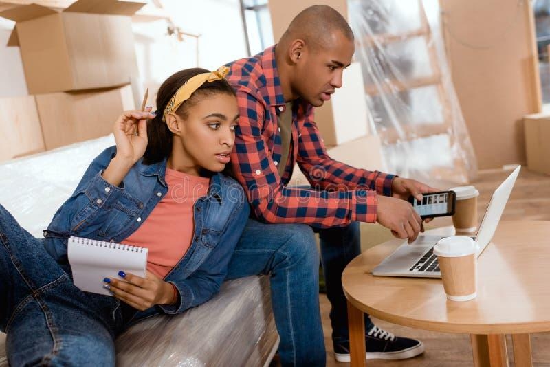 προγραμματισμός ζευγών αφροαμερικάνων με το σημειωματάριο και τις συσκευές στον καναπέ στοκ εικόνες