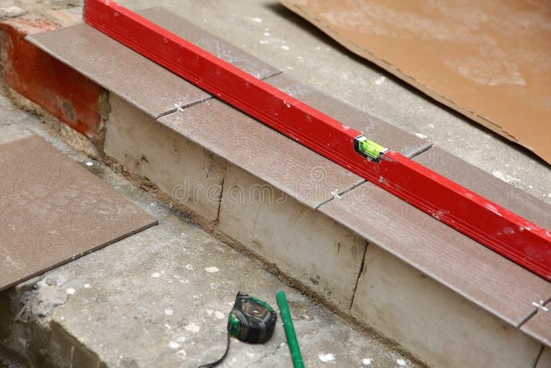 Προγραμματισμός της τοποθέτησης της τερακότας στα σκαλοπάτια, κρατώντας μια ίση θέση με το επίπεδο πνευμάτων στοκ φωτογραφία με δικαίωμα ελεύθερης χρήσης
