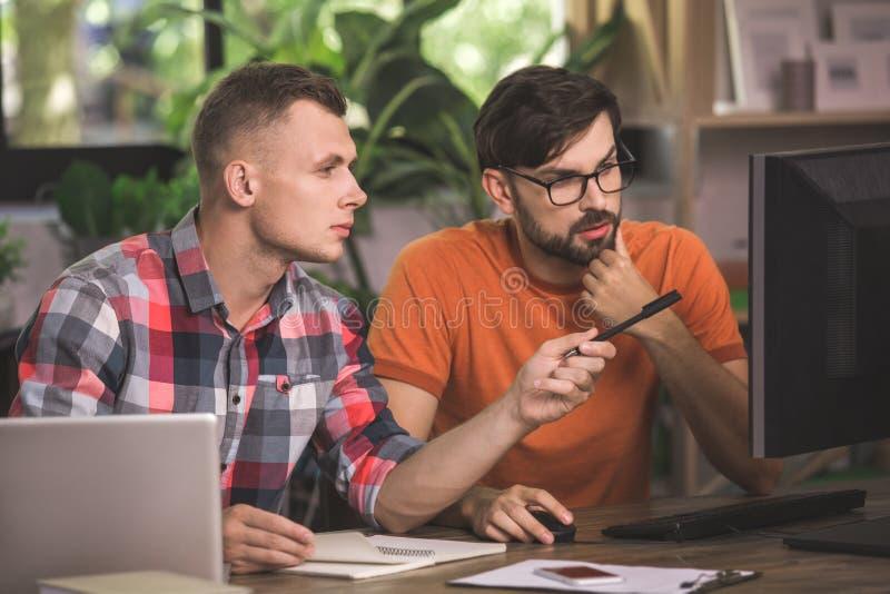 Προγραμματιστές νεαρών άνδρων που εργάζονται μαζί στο γραφείο στοκ φωτογραφία με δικαίωμα ελεύθερης χρήσης