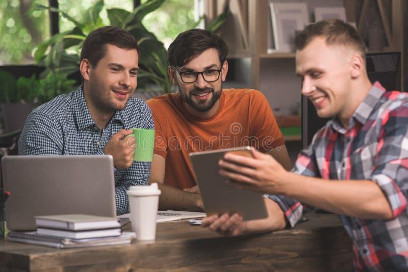 Προγραμματιστές νεαρών άνδρων που εργάζονται μαζί στο γραφείο στοκ εικόνες