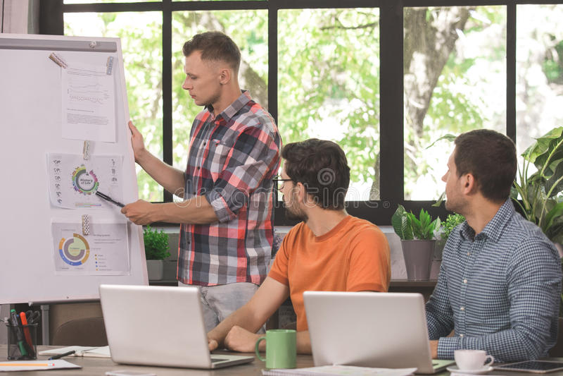 Προγραμματιστές νεαρών άνδρων που εργάζονται μαζί στο γραφείο στοκ εικόνα