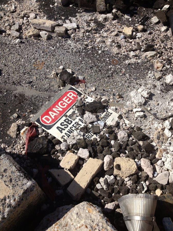 Προειδοποιητικό σημάδι αμιάντων που βάζει μεταξύ των συντριμμιών αμιάντων στοκ εικόνα
