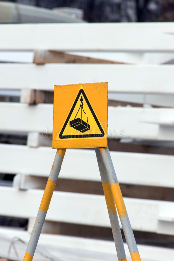 προειδοποιητικό σημάδι μιας πιθανής πτώσης στο φορτίο από έναν γερανό σε ένα κίτρινο υπόβαθρο στοκ εικόνα