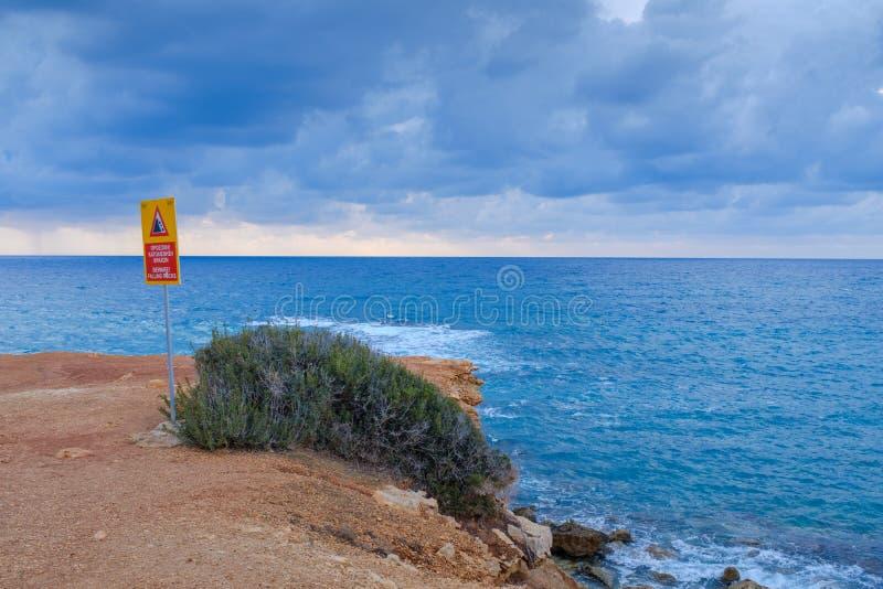 Προειδοποιητικό σημάδι σε έναν απότομο απότομο βράχο στοκ εικόνα με δικαίωμα ελεύθερης χρήσης