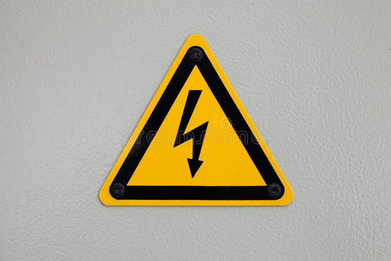 Προειδοποιητικό σημάδι τριγώνων υψηλής τάσης που τοποθετείται σε γκρίζο στοκ φωτογραφία
