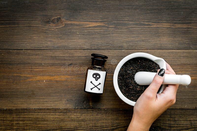Προετοιμάστε το δηλητήριο Μπουκάλι με το κρανίο και crossbones κοντά στο χέρι που κάνει τη σκόνη στο κονίαμα στη σκοτεινή ξύλινη  στοκ εικόνα