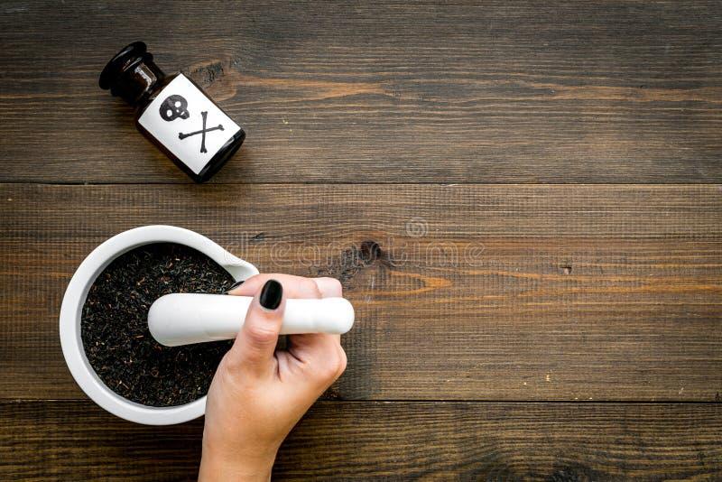 Προετοιμάστε το δηλητήριο Μπουκάλι με το κρανίο και crossbones κοντά στο χέρι που κάνει τη σκόνη στο κονίαμα στη σκοτεινή ξύλινη  στοκ φωτογραφία με δικαίωμα ελεύθερης χρήσης