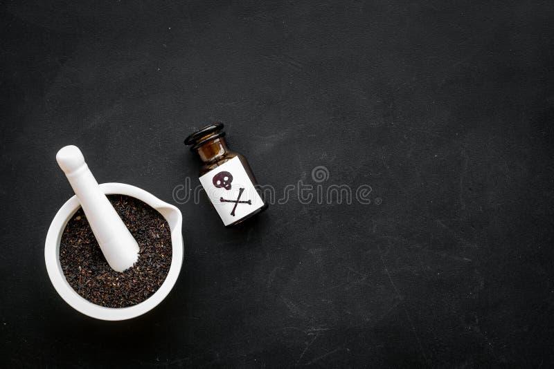 Προετοιμάστε το δηλητήριο Μπουκάλι με το κρανίο και crossbones κοντά στο κονίαμα και pounder στο μαύρο διάστημα αντιγράφων άποψης στοκ φωτογραφία