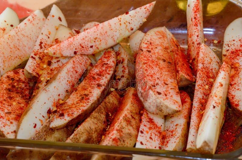 Προετοιμαμένος να μαγειρεψει τις σφήνες πατατών με το τσίλι και την πάπρικα, ζωηρόχρωμα τρόφιμα στοκ φωτογραφία με δικαίωμα ελεύθερης χρήσης
