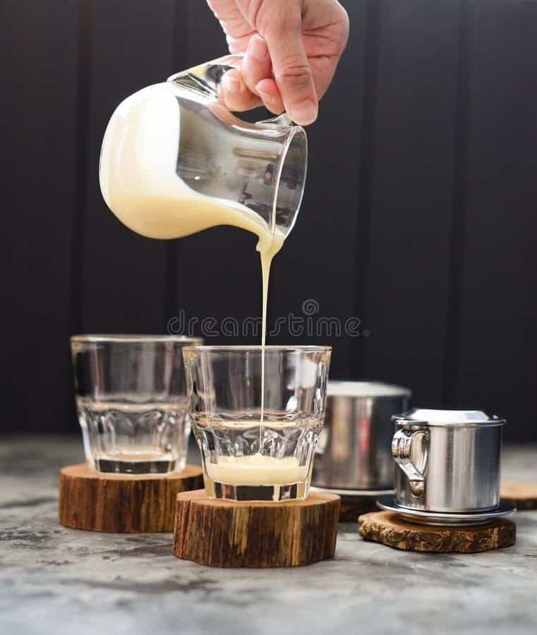 Προετοιμαμένος τα βιετναμέζικα χύνουν πέρα από τον καφέ Χέρι γυναικών που χύνει το συμπυκνωμένο γάλα στα γυαλιά στο σκοτεινό υπόβ στοκ εικόνα