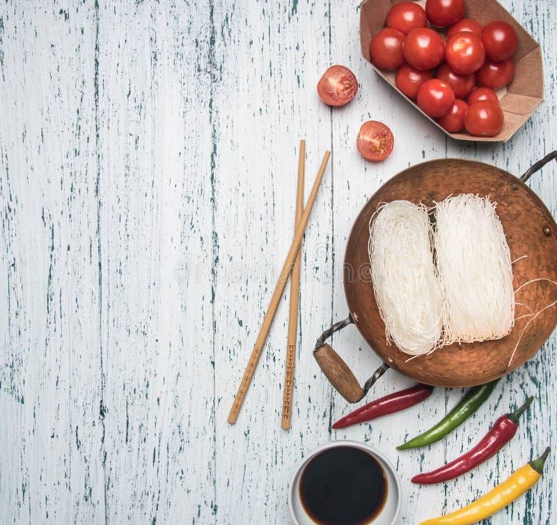 Προετοιμασία έννοιας Funchoza με το καυτές πιπέρι, τις ντομάτες και τη σάλτσα σόγιας, στο ελαφρύ αγροτικό ξύλινο υπόβαθρο, διάστη στοκ εικόνες