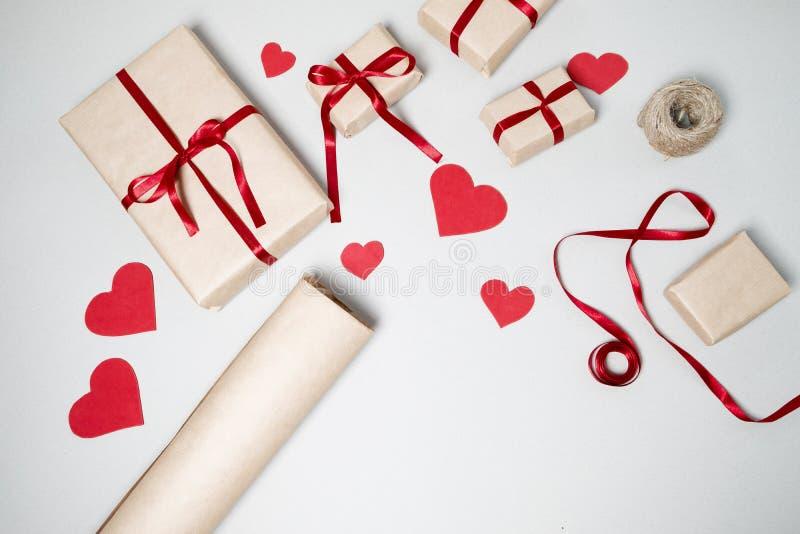 Προετοιμασία για την ημέρα βαλεντίνων με τα κιβώτια δώρων, κόκκινη κορδέλλα και αυτός στοκ εικόνες