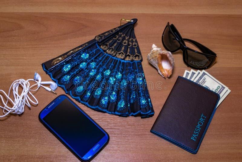 Προετοιμασία για τη διακινούμενη έννοια, τα χρήματα, το διαβατήριο, το ακουστικό, τον ανεμιστήρα, το κινητό τηλέφωνο και τα γυαλι στοκ εικόνα