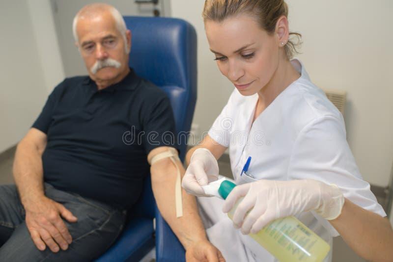Προετοιμασία για τη εξέταση αίματος με τον όμορφο νέο ξανθό γιατρό στοκ φωτογραφίες