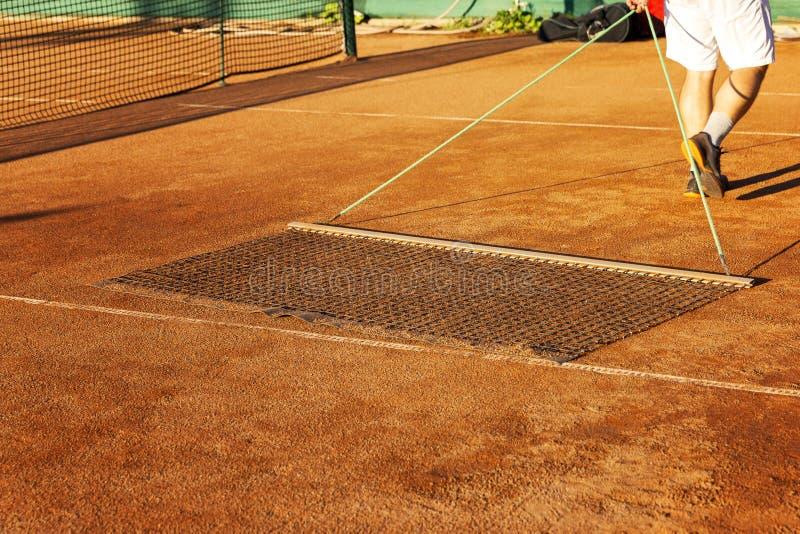 Προετοιμασία ενός γηπέδου αντισφαίρισης για την αντιστοιχία Το άτομο ευθυγραμμίζει την επίγεια κάλυψη στοκ εικόνα με δικαίωμα ελεύθερης χρήσης