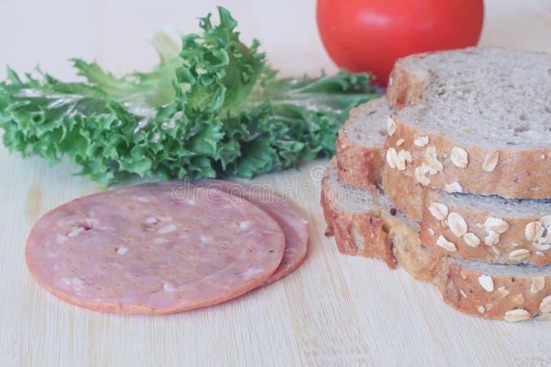 Προετοιμασία ολόκληρων του ψωμιού και του ζαμπόν σίτου για να κάνει το σάντουιτς στοκ φωτογραφία
